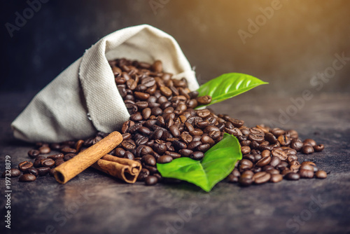 Pile of coffee beans and green leaves in bag on dark background - 197328879