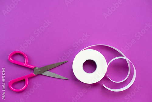 Scissors and a roll of tape white on a purple background. - 197337865