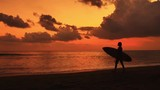 Silhouette of female surfer walking on beach and carrying surfboard at sunset with beautiful dramatic clouds on orange sky. Slow motion video of summer vacations and holidays on tropical coast od Bali - 197339482