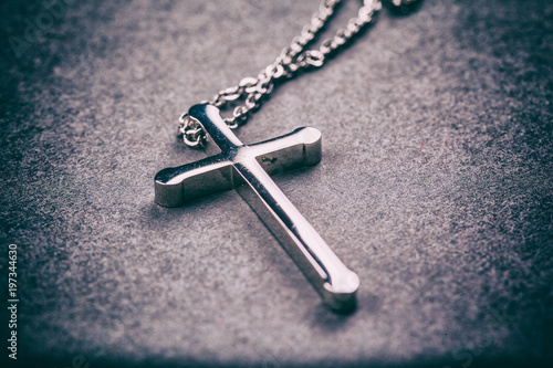Silver cross on a gray background - 197344630