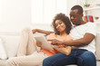 Black couple making using digital tablet at home