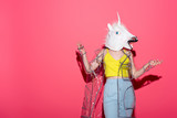 Fototapety funny woman in fashionable transparent raincoat and unicorn mask on red
