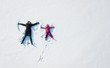Child girl and mother playing and making a snow angel in the snow. Top flat overhead view