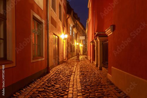 Fotobehang Rood paars Riga. Old street at night.
