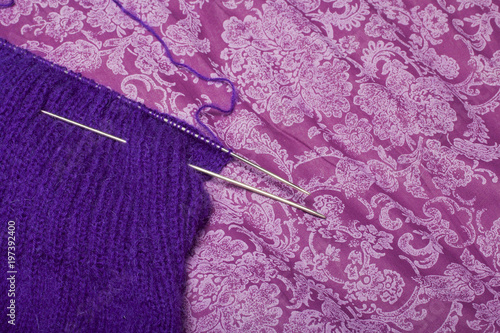 The knitted garment is purple with stuck knitting needles and tangles of thread, of which it is knitted.