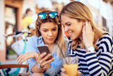 Two young women online via a smartphone in cafe - 197394819