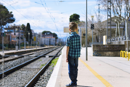 Fototapeta boy waiting for train at railway station in spring