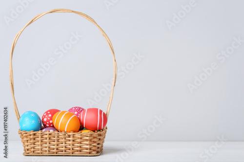 Kolorowi Easter jajka w koszu na popielatym tle