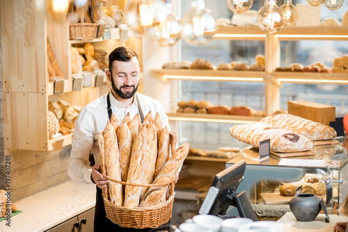 Handsome bread seller with basket full of baguettes in the beautiful store with bakery products