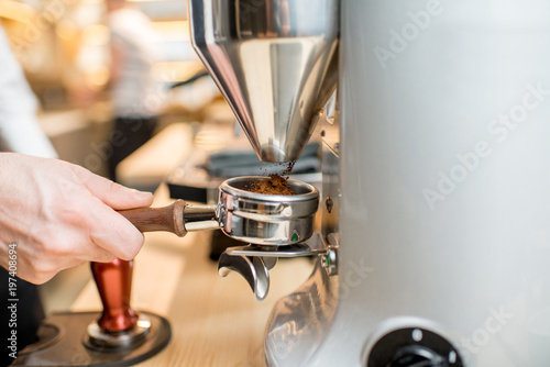 Grinding a coffee into the handle of the professional coffee machine - 197408694