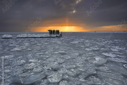 Foto op Canvas Zee zonsondergang Frozen wooden breakwaters line to the world war II torpedo platform at Baltic Sea, Babie Doly, Poland