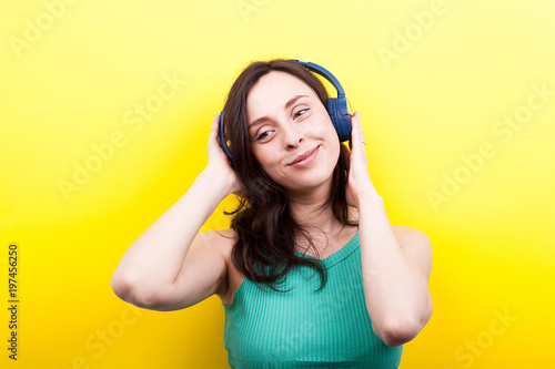 Happy smiling woman listening to music on yellow background in studio