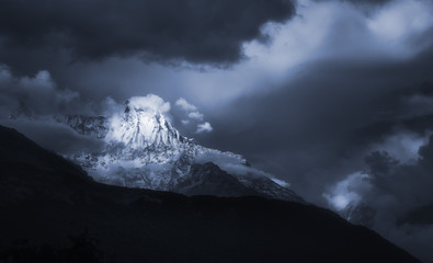 Scenic landscape with mountain peak Annapurna in overcast dramatic cloud sky.