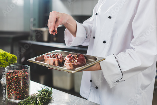 cropped image of chef adding spices to raw steaks at restaurant kitchen - 197479431