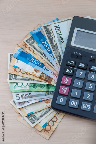 Different banknotes of different denominations are stacked in a fan and a calculator on the table vertically. - 197485690