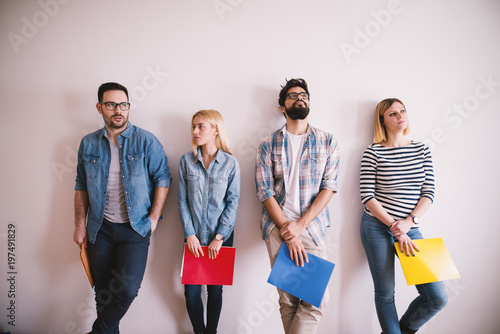 Group of young stylish people leaning against the wall bored before a job interview with folders in hands in the waiting room.