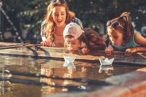 Mother and her daughters playing with paper boats in the fountain in garden.