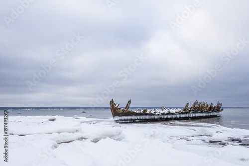 Fotobehang Schipbreuk Old broken boat wreck and rocky beach in wintertime. Frozen sea, evening light and icy weather on shore like fairy tale country. Winter on coast. Blue sky, white snow, ice covers the land.