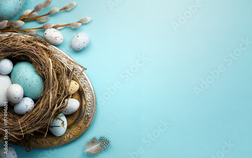 Easter background with Easter eggs and spring flowers on blue table - 197494689