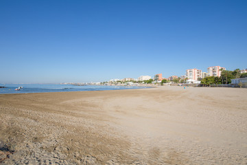landscape Els Terrers Beach, in Benicassim, Castellon, Valencia, Spain, Europe. Lonely sand, buildings, blue clear sky and Mediterranean Sea