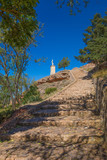 stone stairs climbing to the top of mountain in nature between trees and blue sky, with a statue of Jesus Christ in Ayllon village, Segovia, Spain, Europe