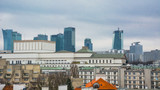 Panoramic view of Warsaw. In the foreground are the roofs of the old city center with tiled roofs. In the background are modern high-rise buildings