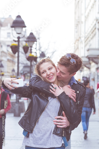 Cute young couple making selfie on the street.