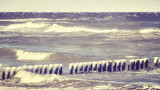 Frozen wooden breakwater on a windy day, Baltic Sea in Poland, color toned picture.