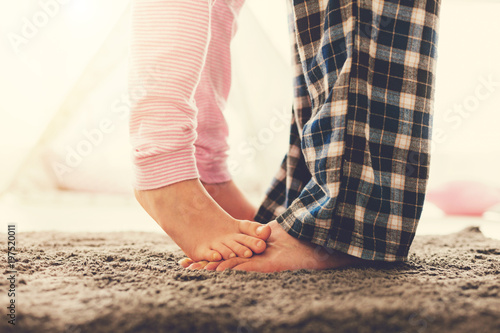 Family relationships. Close up of a cute nice small girl standing on the fathers feet while being at home with him