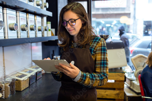 Beautiful young saleswoman doing inventory in a retail store selling coffee. - 197532876