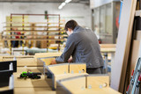 production, manufacture and industry concept - assembler working making furniture at factory workshop - 197533659