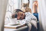 Child relaxing with a cat on a window sill - 197534215
