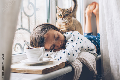Dziecko relaksujące z kotem na parapecie
