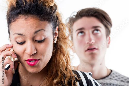 Bored man standing behind woman talking on phone Poster
