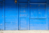 front view of a blue painted wooden house with closed door , window and shutter