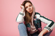 Portrait of a beautiful model in a sports jacket print and jeans sitting on a pink background