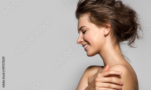 Foto Murales Beautiful woman with perfect skin and bare shoulders in profile on a gray background