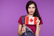 Beautiful brunette woman holding a flag of canada in her hands, on a purple background. Learning a foreign language. Travels.