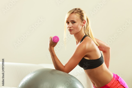 Woman with gym ball and dumbbell doing exercise - 197591064