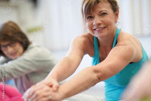 Poster Portrait of senior woman in fitness class exercising on floor