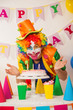 Clowns are a boy in bright costumes at the child's birthday. A table with refreshments and a cake. The explosion of emotions and the fun of the circus. greed and desire to eat cake