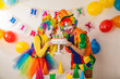 Clowns are a boy and a girl in bright costumes at the child's birthday. A table with refreshments and a cake. The explosion of emotions and the fun of the circus. greed and desire to eat cake