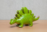 Stegosaurus dinosaur toy on wooden table.