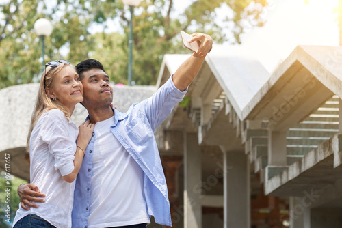 Loving mixed couple taking selfie with smartphone together