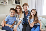 Portrait Of Smiling Family Sitting On Sofa At Home Together