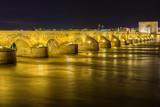 puente sobre río guadalquivir con mucha agua, larga exposición de noche