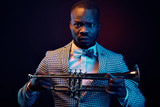 Neon portrait of handsome black jazzman in plaid jacket with floral bow tie with trumpet in his hands. Orange and blue studio light