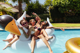 Group of friends on vacation having fun in swimming pool