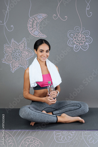 Productive morning. Positive pretty sporty woman smiling and feeling satisfied with her morning training while sitting on a comfortable yoga mat and holding a bottle of water