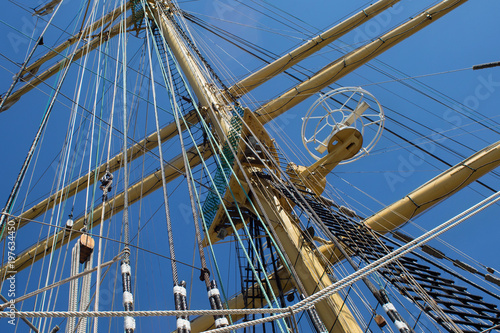 Foto op Plexiglas Schip Masts of a sailing ship with the lowered sails with blue sky on the background.